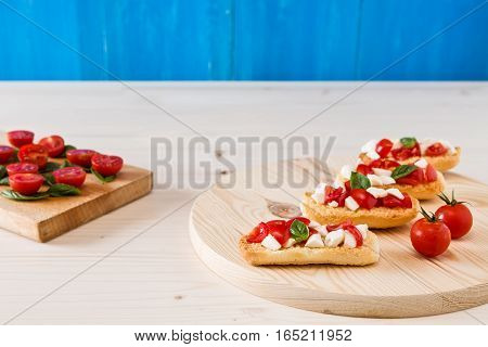 Italian crostini with mozzarella cherry tomatoes and basil on a chopping board and blue background