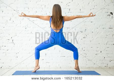 Young attractive woman practicing yoga, standing in Goddess exercise, Sumo Squat pose, working out, wearing sportswear, blue suit, indoor full length, white loft studio background, rear view
