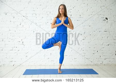 Young happy attractive woman practicing yoga, standing in Vrksasana exercise, Tree pose with Namaste, working out, wearing sportswear, blue suit, indoor full length, white loft studio background