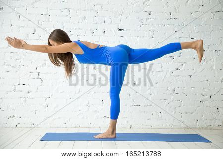 Young attractive woman practicing yoga, standing in Warrior three exercise, Virabhadrasana III pose, working out, wearing sportswear, blue suit, indoor full length, white loft studio background