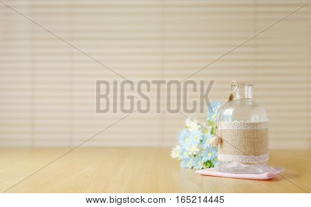 Empty bottle with hemp sack cloth wraped with flower with copyspace selective focus on bottle shallow depth of field