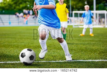 Running Soccer Player. Children Football Soccer Match. Kids Playing Soccer Game Tournament. Boys Running and Kicking Football. Youth Soccer Stadium in the Background