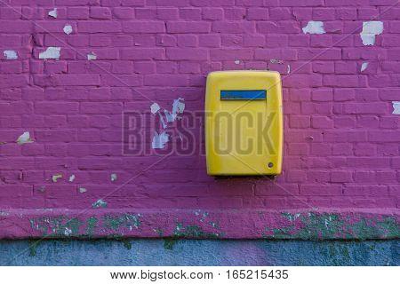 Yellou Postbox on Crack Stoun Wall Purple