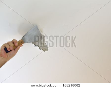 Man's hand holding a plaster spatula peeling a ceiling preparing it for smoothing