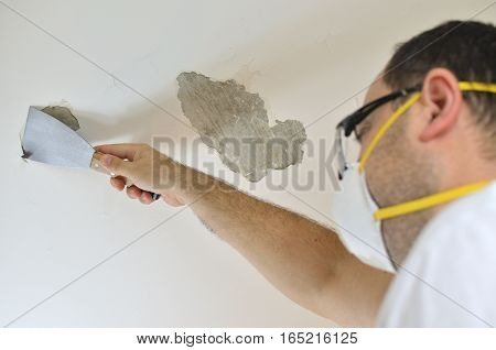 Man holding a plaster spatula peeling a ceiling preparing it for smoothing