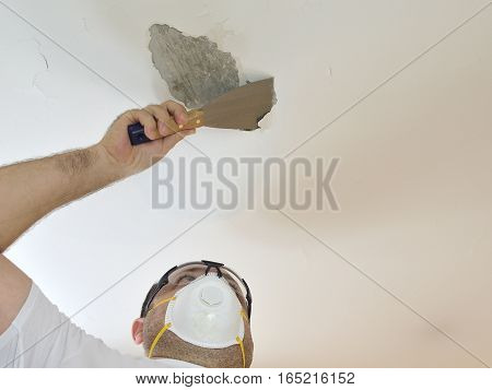 Man with protecting mask holding a plaster spatula peeling a ceiling preparing it for smoothing