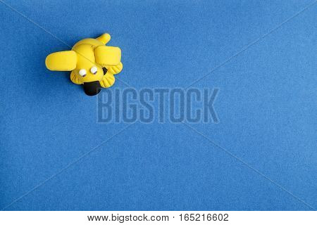 Dog from plasticine on a blue background the top view