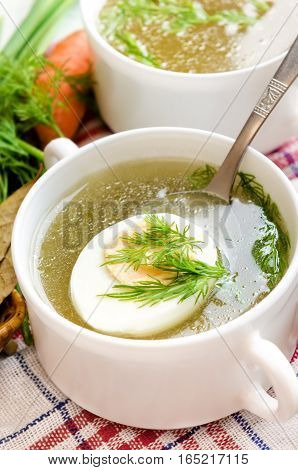 Chicken bouillon with egg and dill in the white bowl.