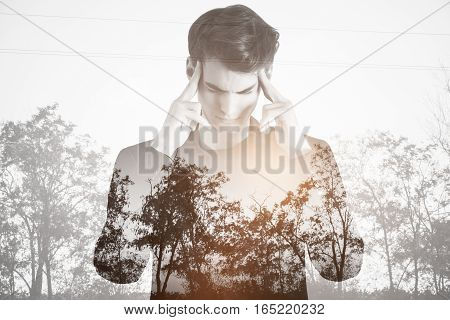 Pensive young guy on dull landscape background. Apathy concept