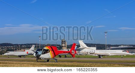 Kloten, Switzerland - 29 September, 2016: Eurocopter EC-120B Colibri helicopter and two Dassault Falcon 7X jets in the Zurich Airport. Zurich Airport, also known as Kloten Airport, is the largest international airport in Switzerland.
