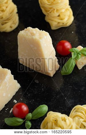 Pasta Tagliatelle parmesan arranged on marble table. Delicious dry uncooked ingredients for traditional Italian cuisine dish. Raw closeup background. Top view. Copy space