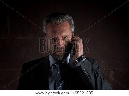 Portrait of a mature businessman in a black suit on dark background