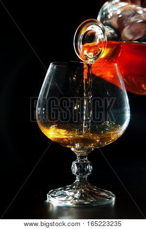 Cognac is poured from a bottle into a glass on a black background