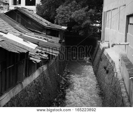 Slums near dirty ditch in black white theme photo taken in Jakarta Indonesia java