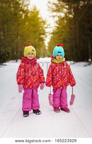 Two girls are standing on snowy road in the woods
