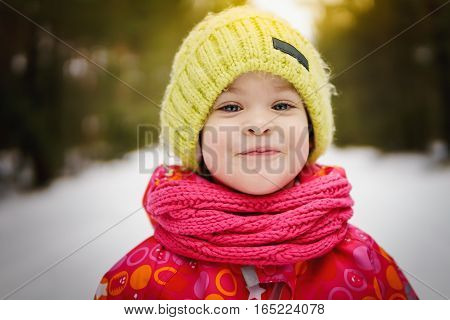 little girl on a walk in the winter snow-covered forest