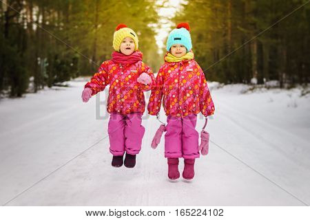 Two girls are jumping on a snowy road in the woods