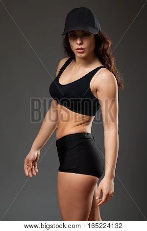Young sports woman in a black top and shorts and a cap, half turned , gray background