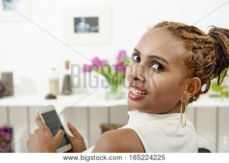 cut african american woman sitting on sofa using mobile phone