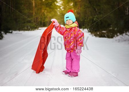 girl posing with sledge on snow-covered road in forest