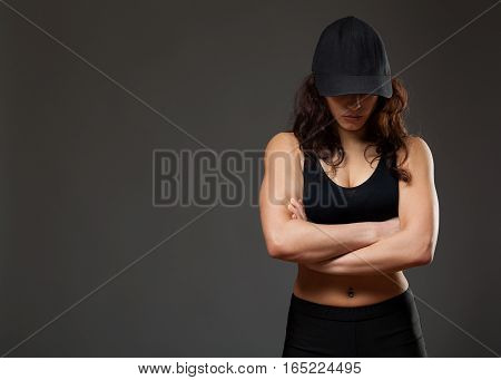 Young athletic woman in a black cap, the head is lowered, hands are crossed, gray background