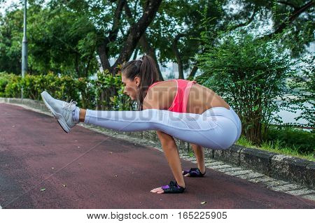 Side view of sporty young woman standing in yoga firefly position in park. Fit girl doing handstand exercise outdoors on summer day.