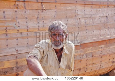 MANDVI, GUJARAT, INDIA - DECEMBER 21, 2013: Portrait of a Gujarati man sitting in front of a traditional wooden Dhow