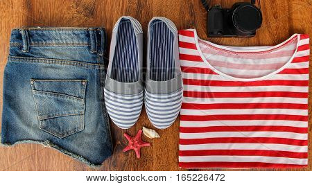 Set clothes for going to sea: jeans shorts, a striped shirt and striped sneakers, photocamera, shells, a top view of a wooden background