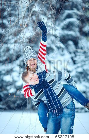 happy pair of male and female embracing and having fun wearing warm clothes outside