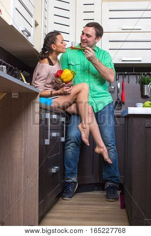 Portrait Of Amorous Couple With vegetables In The Kitchen.