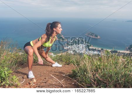 Slim young woman doing side lunge stretching exercise on top of the mountain with sea and sky in background.