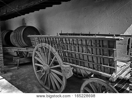 Spain, Catalonia. One of the many wineries with wine cellar (Bodega in Spanish). Entourage for tourists - old trucks for transportation of grapes, grape harvesting carts, wooden barrels of different sizes and other utensils. poster