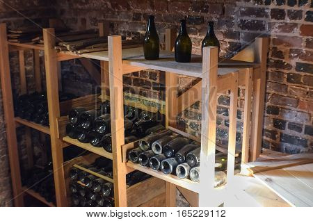 Old rustic bottles of wine in cellar wooden shelves against brick wall