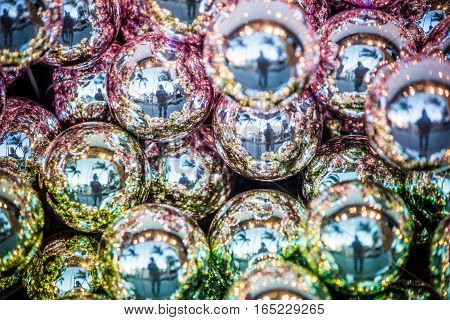Sparkling shiny green and purple Christmas ornaments with reflection of person