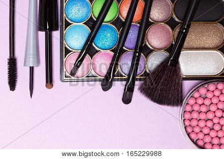 Decorative cosmetics for holiday party makeup. Blush, color glitter eyeshadow, liquid eyeliner, mascara with applicator and brushes