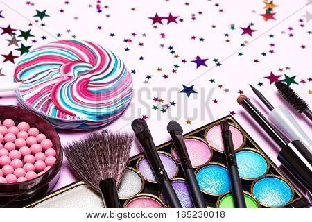Decorative cosmetics for holiday party make up. Blush, color glitter eyeshadow, liquid eyeliner, mascara, brushes with lollipop and confetti