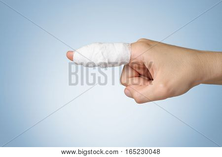Injured painful finger with white gauze bandage
