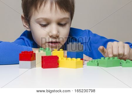 Little kid boy playing with colourful plastic construction toy blocks at home. Children, education, toys, leisure concept