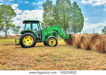 Hay roll bales with tractor on countryside field