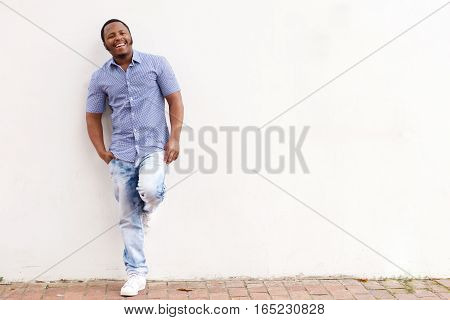 Smiling African American Man Leaning Against White Wall