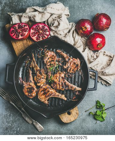 Barbecue dinner. Grilled lamb meat chops with onion and rosemary in black cast iron pan served with fresh pomegranates on wooden board over grey concrete background, top view. Slow food concept