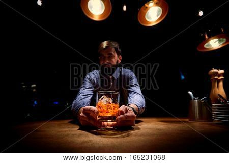 The bartender at  bar with a glass of alcohol in his hands.