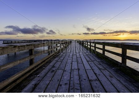 Sunrise on an ocean pier with frosty wood planks and an orange glow.Victoria British Columbia Canada