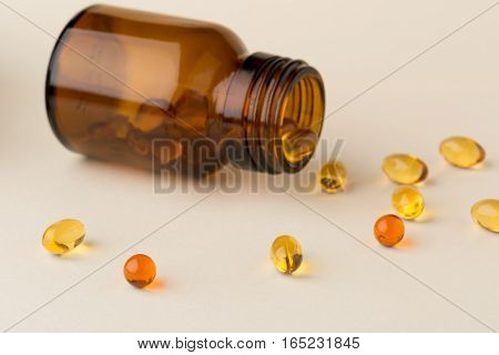 Bottle of pills from the brown glass and fish oil capsules