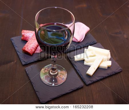 Slices of salami and wine on slate plates on a wooden table