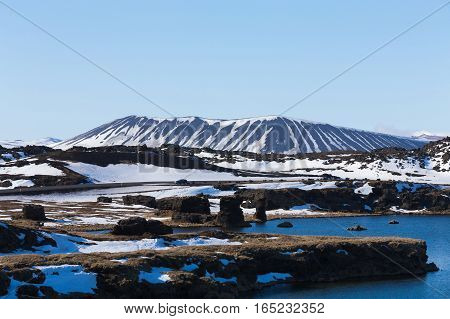 Myvatn volcano over blue lake with clear blue sky background winter season natural landscape background