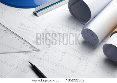 Architectural Blueprints And Blueprint Rolls And A Drawing Instruments On The Worktable