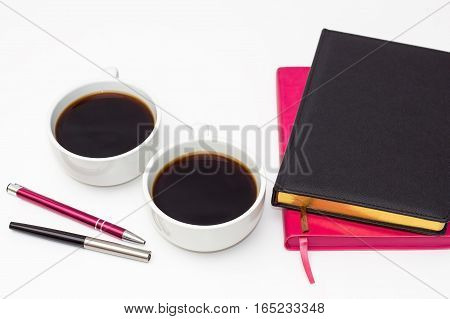 two of the diary two cups of black coffee and pens on a white background. flat lay of the business concept of relationship men and women
