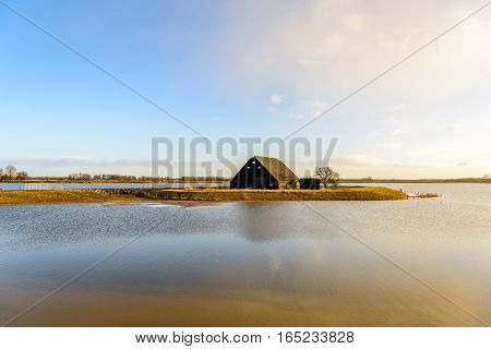 Historic wooden barn from 1900 in a flooded Dutch polder. The polder serves as water storage at high water levels in the adjacent river within the framework of the national project Room for the River.