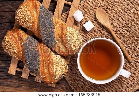 Cup of tea and buns with sesame and poppy seeds on rustic wooden table top view